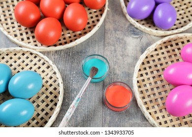 Multicoloured Easter eggs, paintbrush and paints on a wooden table, upper viewpoint
