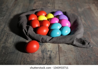 Multicoloured Easter eggs in a textile sack on a wooden table