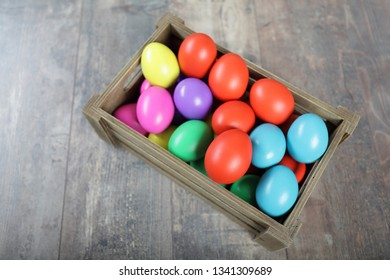 Multicoloured Easter eggs in a wooden box on a table, upper viewpoint