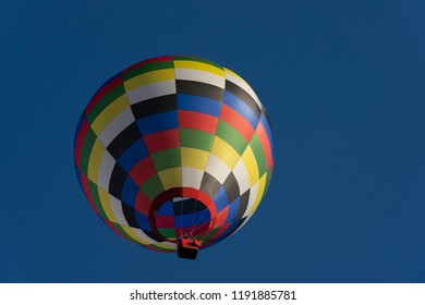 Multi-coloured hot air balloon ascending against a blue sky at Knavesmire,York,North Yorkshire,England,UK.
