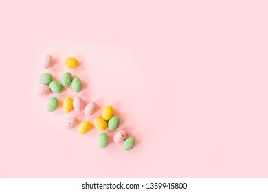 Multicoloured miniture speckled chocolate easter eggs coated in hard shell on pink background, with copy space