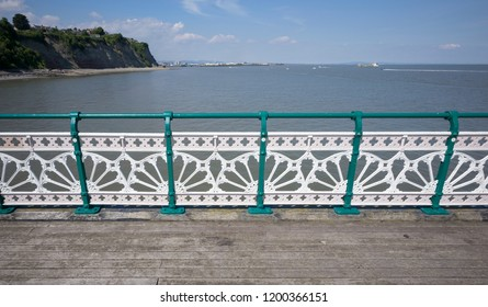 Multicoloured painted cast iron balustrade and railings with traditional pattern along edge of pier, Penarth, south Wales, with coastline behind