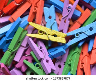 Multicoloured painted wooden mini clothes pegs in random pile. Top down macro photo with selective focus on central yellow peg.