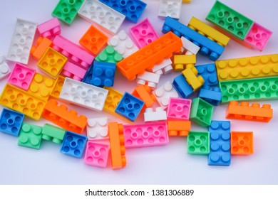 Multicoloured plastic construction blocks or bricks toy on white background