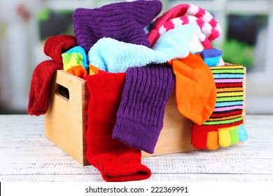 Multicoloured socks in a box on a wooden table in front of the window