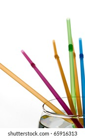 Multi-coloured straws in glass with clear liquid