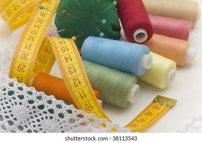 Multi-coloured threads for sewing, needles, a measuring tape on a white canvas