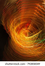 Multicoloured warm lights forming radial starburst light trails. Abstract light swirls motion energy slow shutter