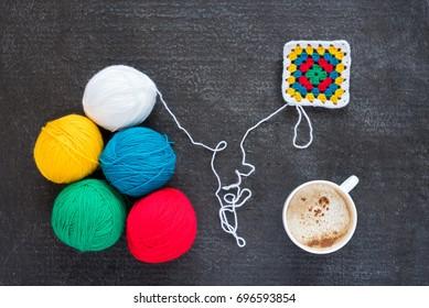 Multicoloured yarn, a crocheted motif and coffee