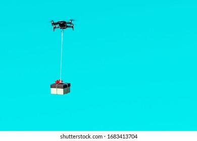 Multicopter-Drohne, die mit einem Geschenkbox einzeln auf hellblauem Hintergrund fliegt, Konzept einer modernen schnellen Liefermethode mit Dronen