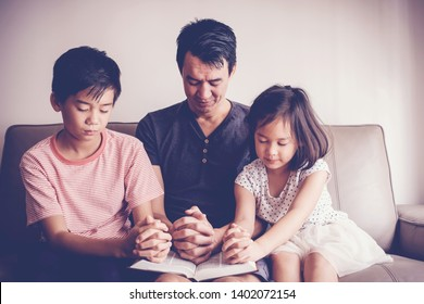 Multicultural Asian children praying with their father at home, parent and children, online family worship, World Day of Prayer,international day of prayer, hope, gratitude,new normal concept