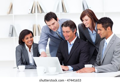 Multi-cultural business team looking at a laptop in the office