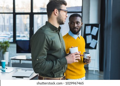 multicultural businessmen talking and holding cups of coffee