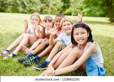 Multicultural children in school trip to nature wave happy