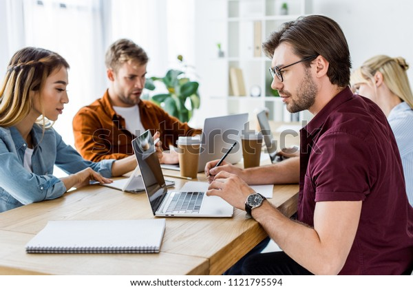 multicultural colleagues working on startup project in office with laptops and coffee