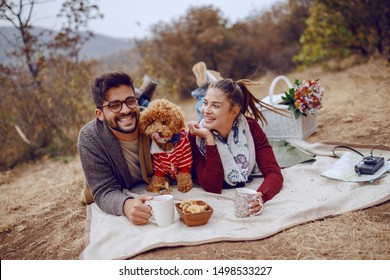 Multicultural couple enjoying day in nature. Couple lying down on blanket with their dog and drinking tea. next to them is basket with flowers and food. Autumn time.