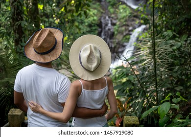 Multicultural couple enjoying waterfall scenery in tropical rainforest. Young mixed race couple on vacation in Asia. Romantic relationship. Love story. View from back. Pengibul waterfall, Ubud, Bali.