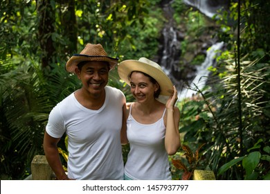 Multicultural couple enjoying waterfall scenery in tropical rainforest. Young mixed race couple on vacation in Asia. Romantic relationship. Love story. Couple in hats. Pengibul waterfall, Ubud, Bali.