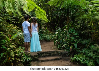 Multicultural couple holding hands on walking trail in tropical rain forest. Young mixed race couple on vacation in Asia. Romantic relationship. Love story. View from back. Ubud, Bali, Indonesia