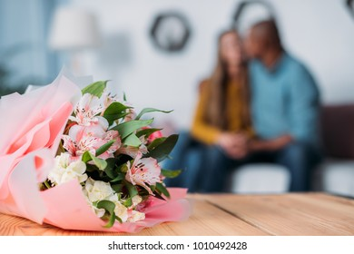 multicultural couple kissing with bouquet on foreground