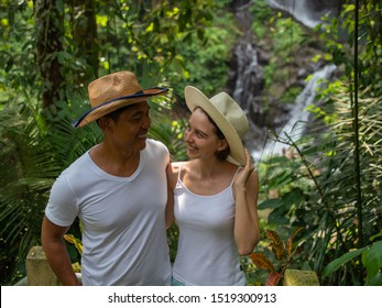 Multicultural couple looking to each other, enjoying waterfall scenery. Young mixed race couple on vacation in Asia. Romantic relationship. Love story. Couple in hats. Pengibul waterfall, Ubud, Bali.
