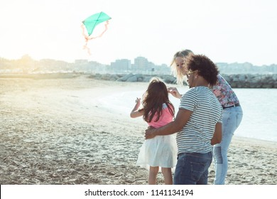 multicultural family with little girl on beach flying a kite at sunset. young parents with child having fun on the beach. concept of diversity, family values quality time and relaxation