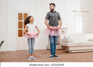 multicultural family in pink tutu tulle skirts dancing at home