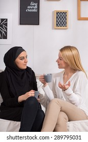 Multicultural female friends drinking coffee and discussing