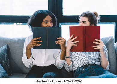 Multicultural female readers looking each other in eyes while sitting on comfortable couch and holding literature books near faces having joyful mood for weekend, concept of knowledge and education