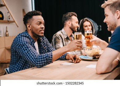 multicultural friends clinking glasses of light beer while spending time together in pub