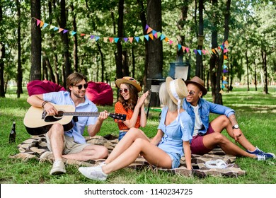 multicultural friends with guitar resting on blanket in summer park