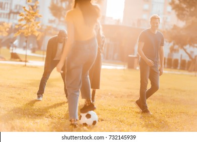 multicultural friends playing soccer together in park