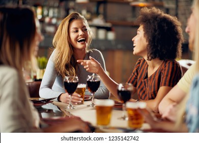 Multicultural friends sitting in restaurant and drinking wine and beer.