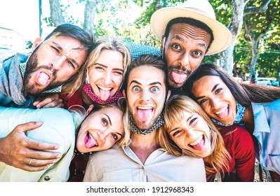 Multicultural friends taking crazy selfie sticking out tongue during Covid 19 third wave - New normal lifestyle concept with young milenial people having fun together - Bright azure sunshine filter