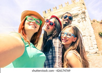 Multicultural friends taking travel selfie at old town roman monument in Italy - Cheerful tourist self photo on ancient arch of Augustus background - Concept of fun using technology on summer holiday