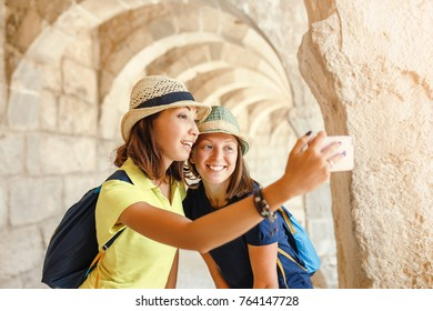 Multicultural girl friends taking travel selfie on a smartphone at old roman ancient town