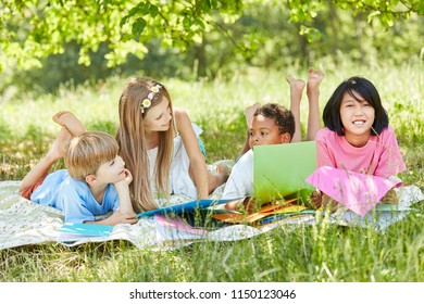 Multicultural group of children on a meadow in summer on vacation
