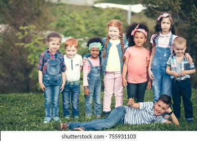 A multicultural group of children in the park on green grass. Friendship Happiness Togetherness Children Casual Concept.