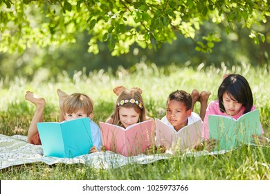 Multicultural group of children reading while studying in the park in summer