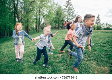 A multicultural group of children running on the grass holding hands. The concept of childhood, friendship, intercultural communication. Full length
