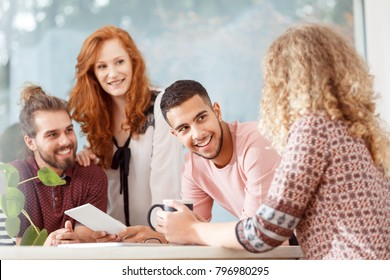 Multicultural group of co-workers smiling during an appointment with boss in the office