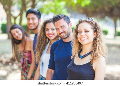 Multicultural group of friends at park. There are three women and two men smiling and looking at camera. They are wearing summer clothes. Selective focus on the girl in foreground.