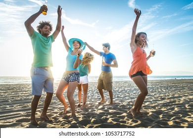 Multicultural group of friends partying on the beach - Young people celebrating during summer vacation, summertime and holidays concepts