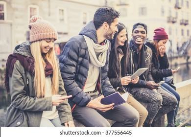 Multicultural group of friends using cellphones - Students sitting in a row and typing on the smartphones, vintage filtered look