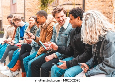 Multicultural group of friends using smartphone and having fun - Happy group of multiracial people addicted to smart phones and social media - Technology concept and millennials lifestyle