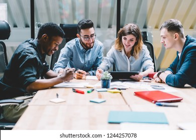 Multikulturelle Gruppe professioneller Designer, die bei der Arbeit mit modernen Touchpad-Gerät während der Brainstorming-Sitzung im Büroinneren zusammenarbeiten. Vier Mitarbeiter diskutieren Arbeit mit Produktivität