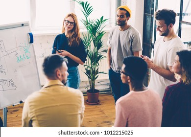 Multicultural group of skilled male and female engineers team working on developing building planning standing near desk in stylish office.Creative students collaborating on new architectural project
