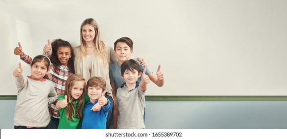 Multicultural group of students holds thumbs up with elementary school teacher