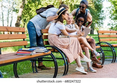 multicultural group of students using tablet while resting on bench in park