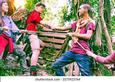Multicultural group of young friends climbing hillside in the forest - Teenagers hands helping each other on steep hiking trail - Concept of teamwork , friendship ,  trekking  main focus at guys hands